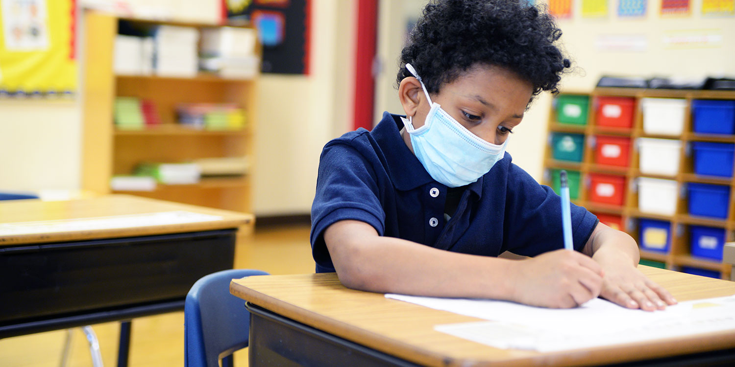 Masked elementary student writing at their desk.
