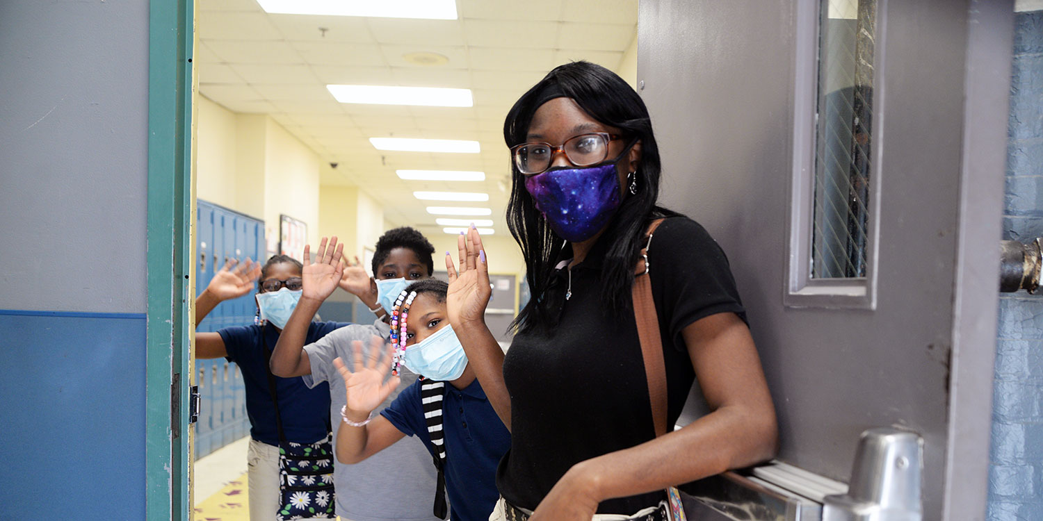 Masked teacher and students waiving through open door.